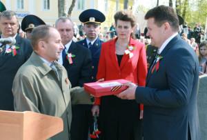 Б. И. Соломатин вручил главе района И. И. Марковичу макет Знамени Победы.