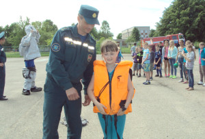 Капитан МЧС А. А. Сятковский  помогает детям справляться с заданием.