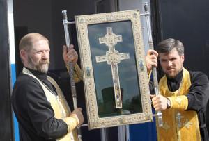 Крест в Свято-Николаевскую церковь вносят священники  о. Пётр и о. Владимир.