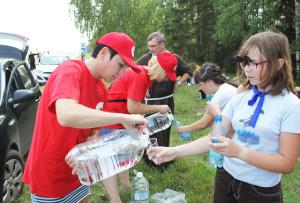 Е. Шамёнок и Е. Витлиф раздают  паломникам воду.