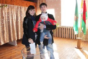 голосует Диана Зуй. С ней на участок пришли муж Евгений и сын Иван.