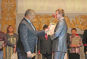 В. В. Быков поздравляет с наградой главного зоотехника СП «Верхнедвинский» С. В. Вильчика.