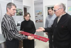 Юрий Карасёв (слева) вручает работникам музея новые экспонаты.