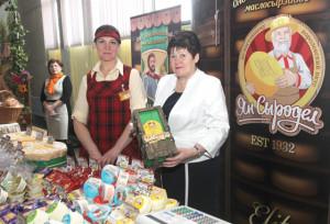 Продукцию маслосырзавода демонстрируют работники предприятия Е. Ковзель и А. Шевернович.