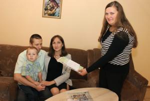 Член избирательной комиссии Т. Б. Зуева вручает приглашение на выборы молодой семье Ляхович из Верхнедвинска.