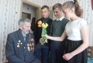 Л. Молодожёнова, К. Павлюкевич, А. Подалевич поздравляют ветерана с праздником.