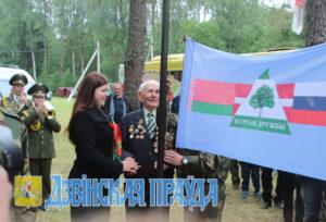 Флаг Кургана Дружбы поднимают  В. В. Дащёнок и Дарья Соколовская.